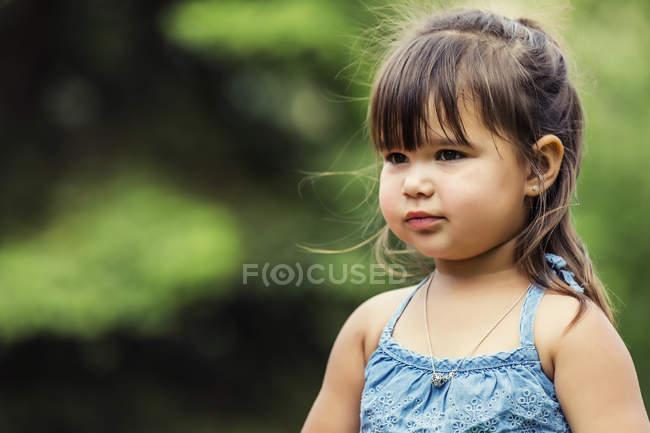Retrato de uma menina linda preschooler olhando para longe contra turva fundo verde — Fotografia de Stock