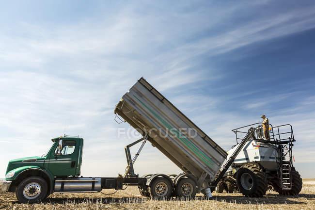 Agricoltore di sesso maschile che lavora con macchinari pesanti in campo — Foto stock