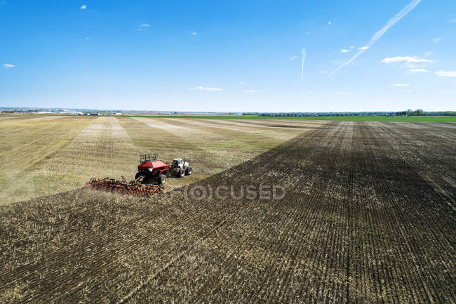 Tractor pulling an air seeder, seeding a field with blue sky in the distance — Stock Photo