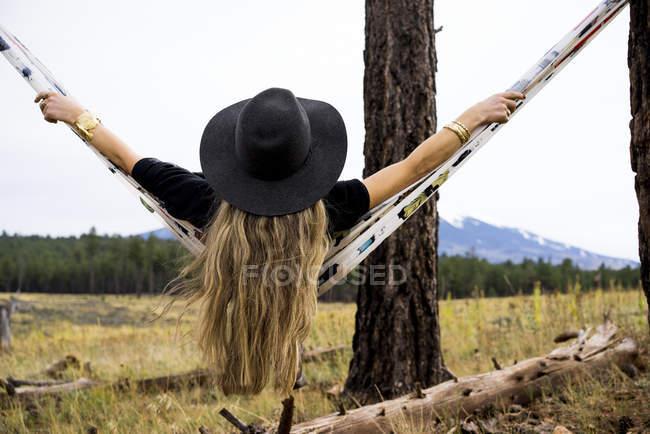 Vue arrière d'une femme assise dans un hamac avec vue sur une montagne, Arizona, États-Unis d'Amérique — Photo de stock