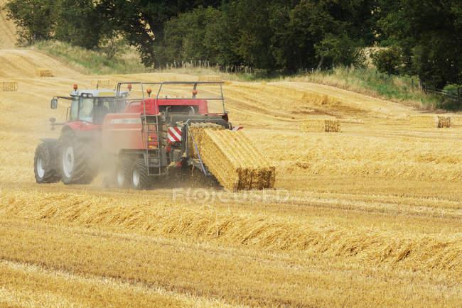 Vista panoramica di trattore balle di fieno in un campo — Foto stock