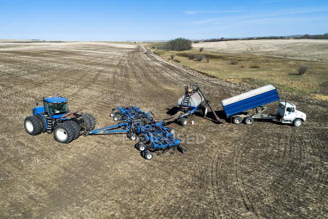 Vista aerea di agricoltore riempire una tramoggia cercatore d'aria con un camion in un campo con cielo blu sullo sfondo — Foto stock