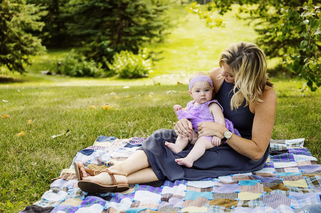 Madre y su hija bebé sentado sobre una manta de picnic - foto de stock
