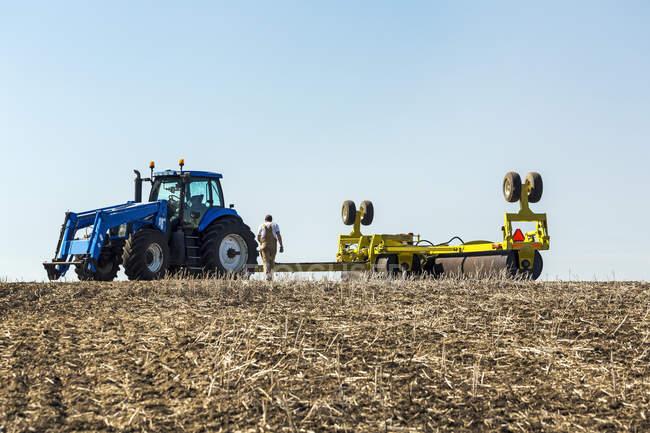 Männlichen Bauern arbeiten mit schwerem Gerät im Feld — Stockfoto