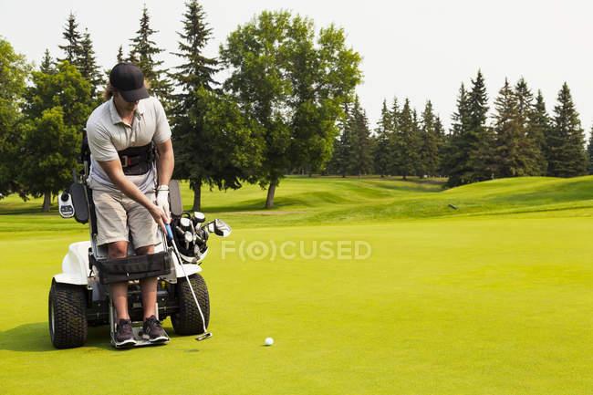 Гольфист с ограниченными физическими возможностями, который ставит мяч на гольф-грин и использует специализированную гидравлическую инвалидную коляску для игры в гольф, Эдмонтон, Альберта, Канада — стоковое фото