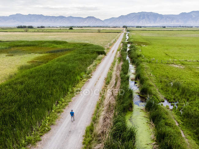 Man walking down a long  road with mountains in the distance, Logan, Utah, USA — Stock Photo