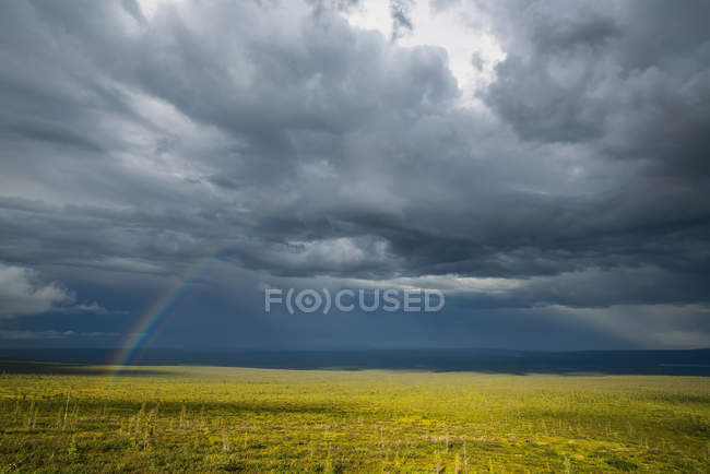 Rainbow through the storm clouds to a field below during a summer storm, near Old Crow, Yukon, Canada — Stock Photo
