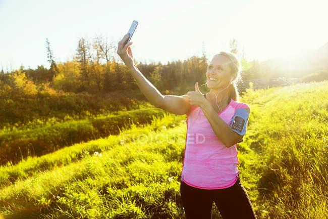 Caucasien mi adulte sportif femme prendre selfie à l'extérieur — Photo de stock