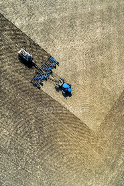 Aerial view of a tractor pulling an air seeder, seeding a