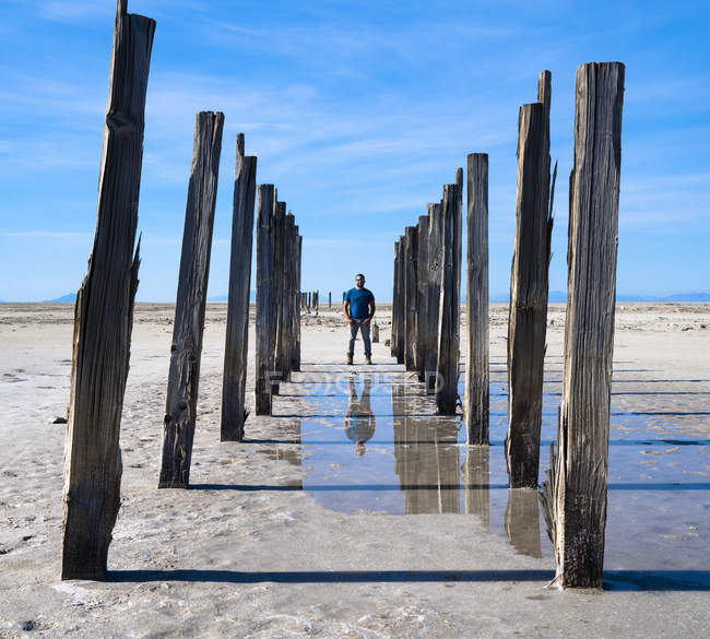 Reflection of man in water standing on barren landscape with wooden posts, Great Salt Lake, Utah, USA — Stock Photo