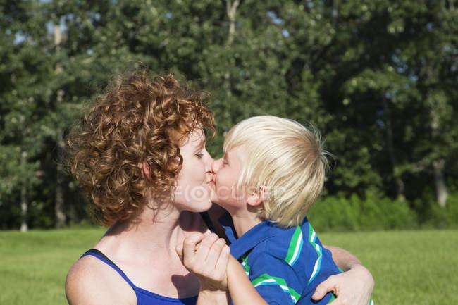 Mère tenant et embrassant son jeune fils — Photo de stock