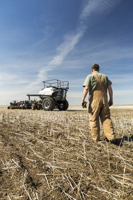 Farmer walking towards hopper and air seeder in a canola stubble field — Stock Photo