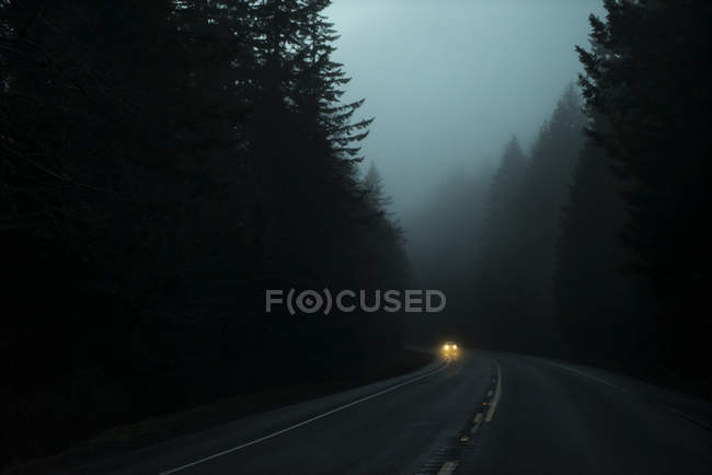 Foggy highway 26 at dusk with headlights on an approaching car, Oregon, United States of America — Stock Photo