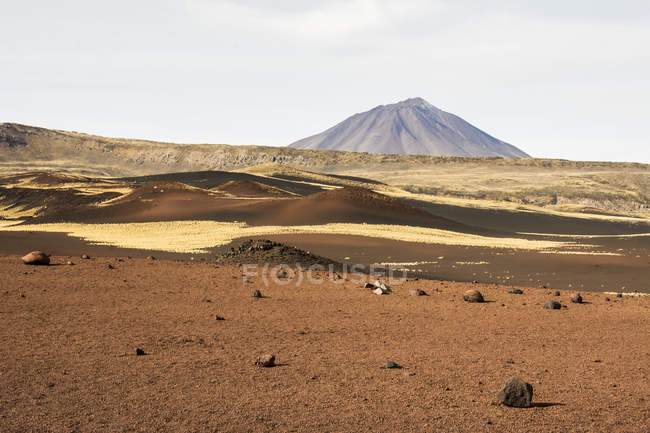 A brown volcanic field leads the eye towards a volcanic peak in the distance, with the crater of the volcano visible, Malargue, Mendoza, Argentina — Stock Photo
