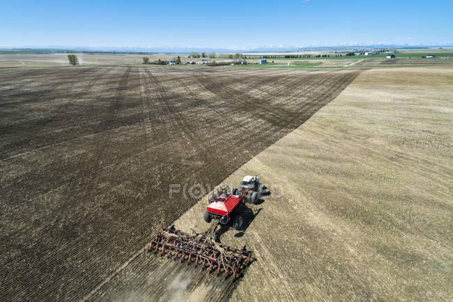 Tractor pulling an air seeder, seeding a field with
