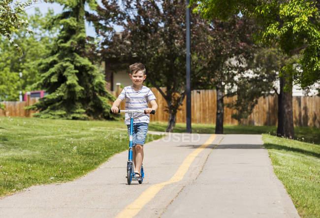 Jeune garçon son scooter à cheval sur un chemin dans un parc de la ville et le sourire pour la caméra, Edmonton, Alberta, Canada — Photo de stock