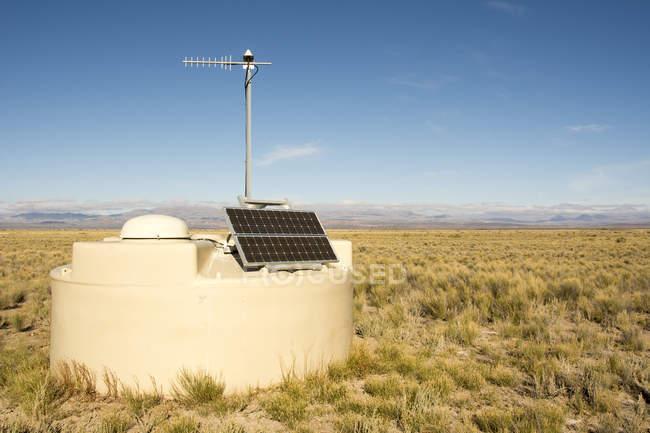 Uno de los detectores de la Pierre Auger, Observatorio es visto de cerca con los Andes en la distancia. El panel solar y la antena son claramente visibles; Malargue, Mendoza, Argentina - foto de stock