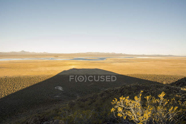 The sunset behind a volcano creates a long shadow over the desert, Malargue, Mendoza, Argentina — Stock Photo