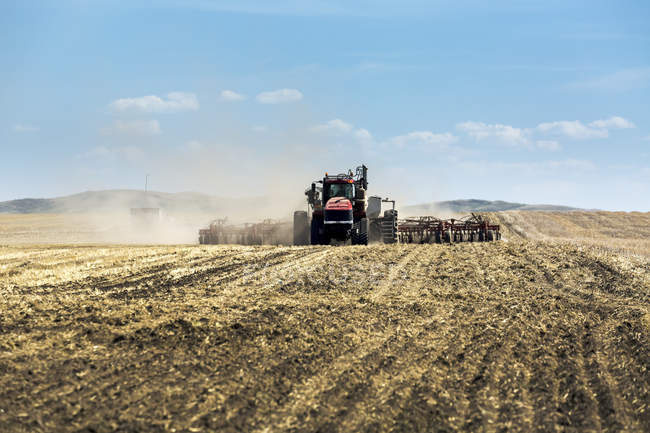 Trattore che tira una air seminatrice, semina un campo con cielo blu e nuvole sullo sfondo — Foto stock