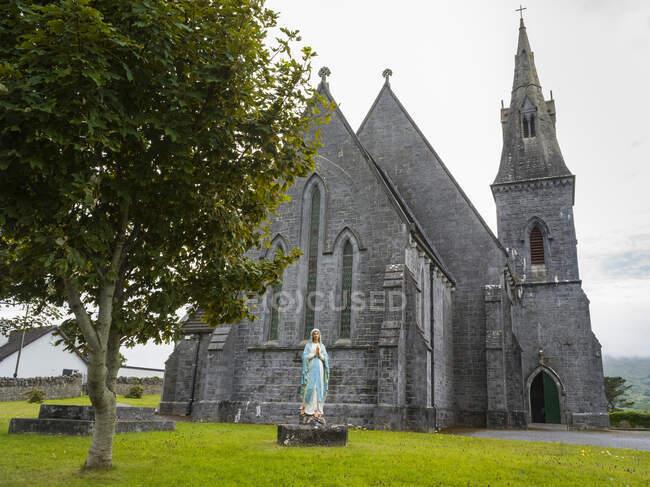 Кам'яна церква з дзвіницею та статуєю молитовної жінки спереду; округ Клер, Ірландія. — стокове фото