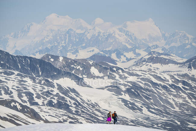 Couple walking on a mountain top with the massive mountains of Kluane National Park and Reserve looming in the distance; Haines Junction, Yukon, Canada — Stock Photo
