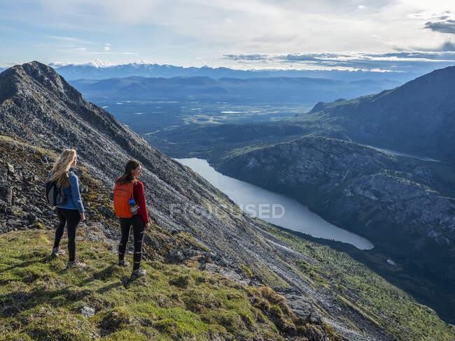 Dos mujeres explorando las montañas y el desierto del Yukón. Sentirse vivo y vibrante en el hermoso paisaje alrededor de Haines Junction; Yukón, Canadá - foto de stock