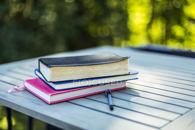 Bible et livres empilés sur une table avec une plume à l'extérieur ; Surrey, Colombie-Britannique, Canada — Photo de stock