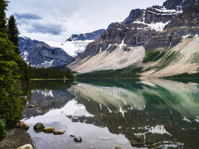 Rugged Canadian Rocky Mountains and glaciers reflected in a tranquil lake, Banff National Park; Improvement District No. 9, Alberta, Canada — Stock Photo