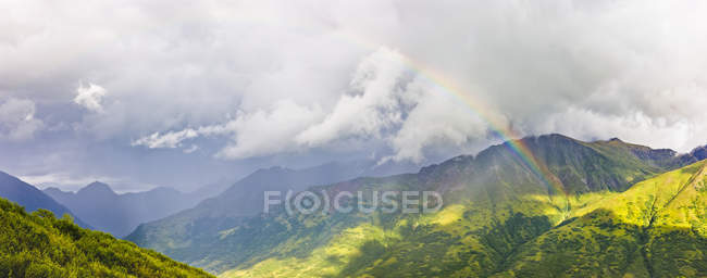 Rainbow shining through atmospheric light, lush green mountainsides in the background, Hatcher Pass, South-central Alaska; Palmer, Alaska, United States of America — Stock Photo