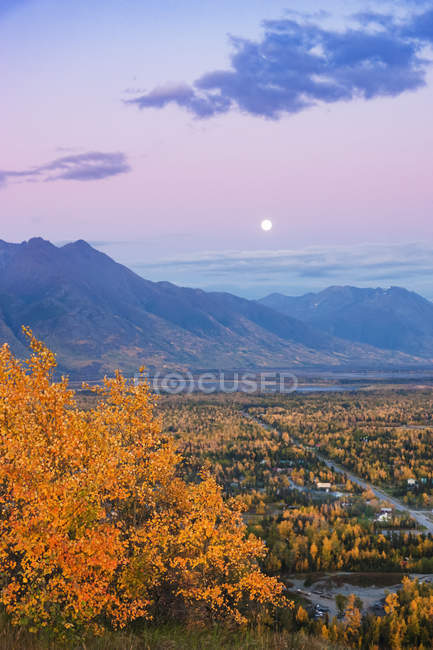 Vista de la luna que se eleva sobre Palmer y el río Knik desde lo alto de la Butte, las montañas Chugach en el fondo durante el crepúsculo en una noche clara, el centro-sur de Alaska, Palmer, Alaska, Estados Unidos de América - foto de stock
