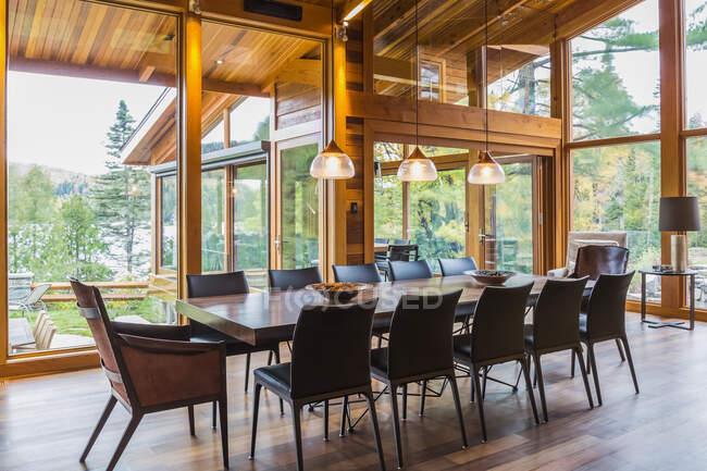 Дерев'яний обідній стіл з малими кріслами, чорними шкіряними кріслами та міддю промислового стилю з морозяними скляними кулонами для освітлення в обідній зоні великої кімнати. — стокове фото