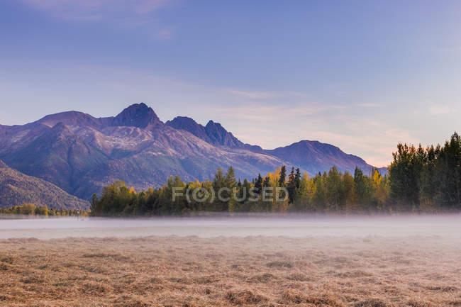 Fog above grassy field below Twin Peaks and the Chugach Mountains during sunset in the Knik River Valley in autumn, South-central Alaska; Palmer, Alaska, Estados Unidos de América. - foto de stock