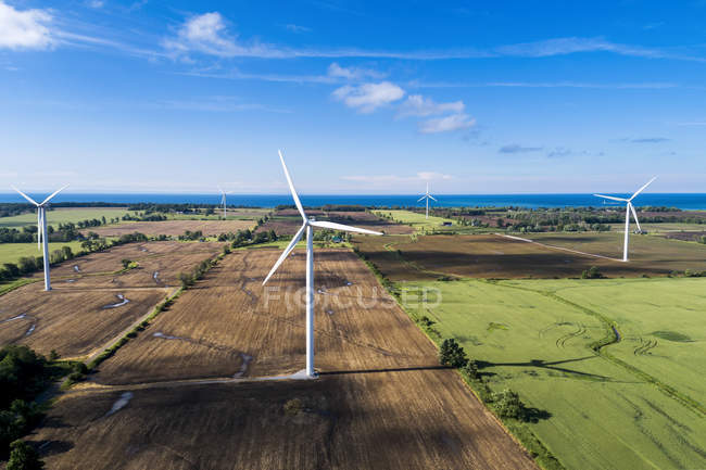 Large wind turbines on farm fiels with a lake in the background and blue sky with clouds, West of Port Colborne; Ontario, Canada — Stock Photo