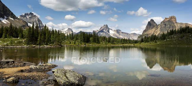 Vue panoramique de la chaîne de montagnes qui se reflète sur un lac alpin avec un rivage rocheux et un ciel et des nuages bleus ; Colombie-Britannique, Canada — Photo de stock