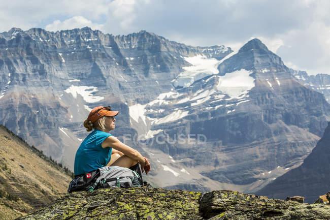 Escursionista femminile seduto su una zona rocciosa che domina vista montagna sullo sfondo; Columbia britannica, Canada — Foto stock
