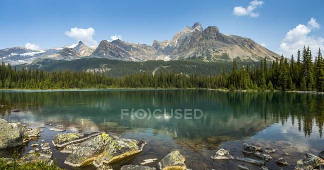 Живописный вид на горный хребет, отражающийся на альпийском озере с скалистой береговой линией и голубым небом и облаками; Британская Колумбия, Канада — стоковое фото