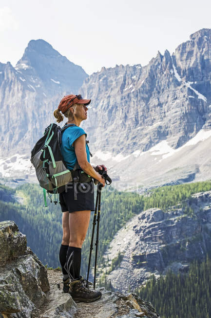 Female hiker standing on cliff edge overlooking mountains and valley; British Columbia, Canada — Stock Photo