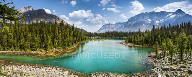 Scenic view of alpine lake with mountains, blue sky and clouds in the background; British Columbia, Canada — Stock Photo