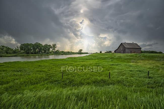 Fienile abbandonato con nubi temporalesche che convergono sopra la testa; Nebraska, Stati Uniti d'America — Foto stock