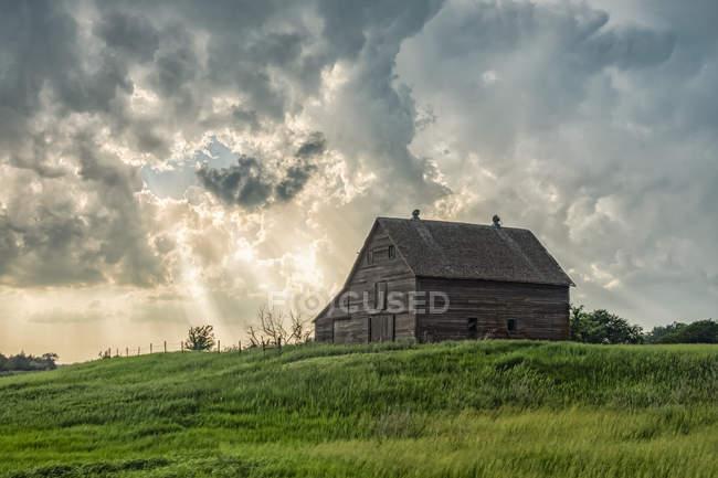 Grange abandonnée avec nuages d'orage convergents au-dessus ; Nebraska, États-Unis d'Amérique — Photo de stock