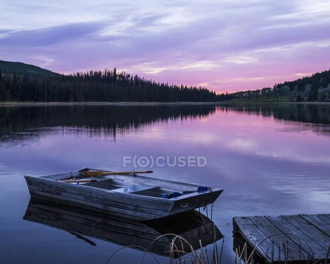 Barque à rames en bois à côté d'un quai sur un lac paisible qui reflète le rose d'un coucher de soleil, parc provincial Lac Le Jeune ; Kamloops (Colombie-Britannique) Canada — Photo de stock