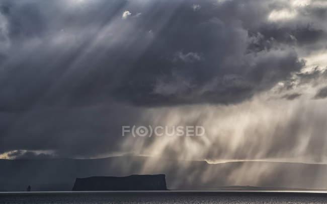 Nuages d'orage spectaculaires et lumière au-dessus d'une île au large des côtes de l'Islande ; Islande — Photo de stock