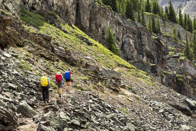 Un gruppo di escursionisti lungo un sentiero roccioso di montagna con scogliere rocciose sullo sfondo; British Columbia, Canada — Foto stock