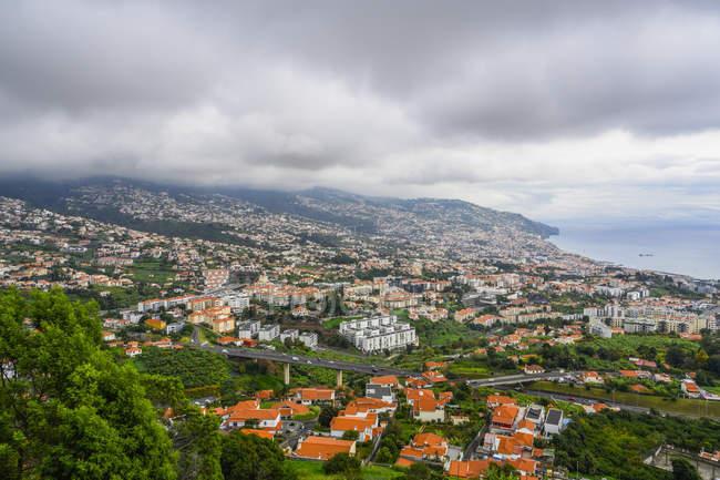 Olhando para baixo nos telhados alaranjados das casas em Funchal, madeira, com o porto na distância distante; Funchal, madeira, Portugal — Fotografia de Stock