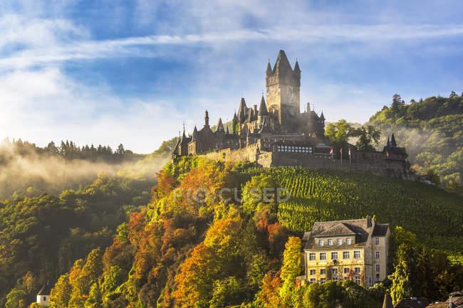 Большой средневековый замок на цветущем склоне холма с туманом, голубым небом и облаками, Кохем, Германия — стоковое фото