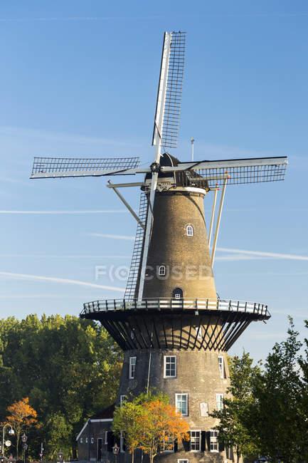 Antiguo molino de viento de madera en la parte superior de la estructura con cielo azul; Leiden, Países Bajos - foto de stock