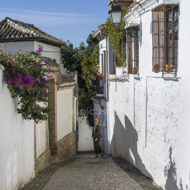 Жінка стоїть на вузькій стежці між стінами будинків з побіленим миром; Гранада (Іспанія). — стокове фото