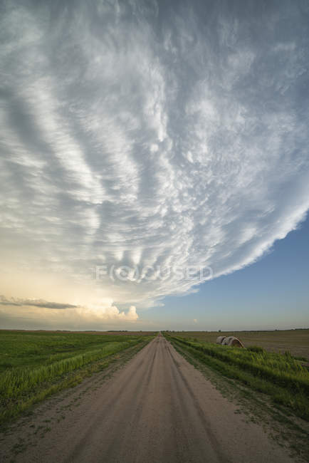 Cieli drammatici su una strada sterrata e paesaggio visto durante un tour inseguimento tempesta nel Midwest degli Stati Uniti; Kansas, Stati Uniti d'America — Foto stock