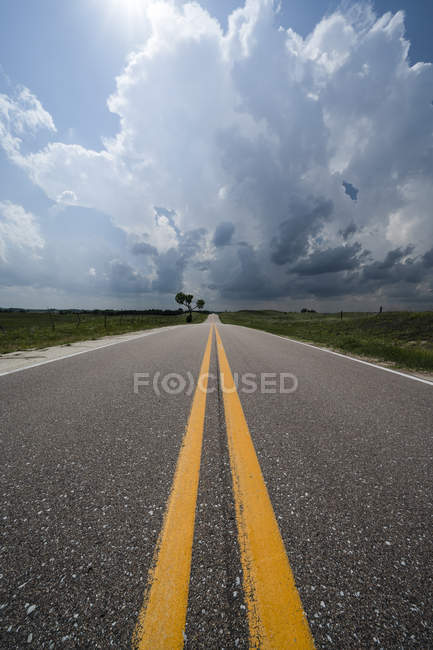 Dramatic skies over the road and landscape seen during a storm chasing tour in the midwest of the United States; Kansas, United States of America — Stock Photo