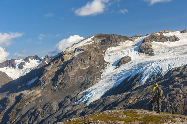 Mann wandert in der Nähe des harding icefield trail mit den kenai Mountains und einem namenlosen hängenden Gletscher im Hintergrund, kenai fjords nationalpark, kenai halbinsel, südzentral alaska, vereinigte staaten von amerika — Stockfoto